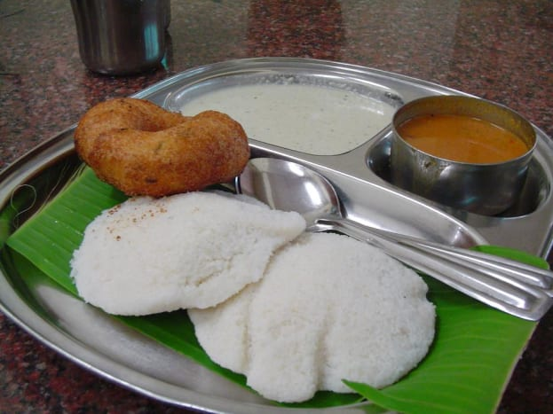The idli is in white. The brown colored round dish is vada which is also many times served with idli sambhar if asked for it. Vada is made by frying a batter of dal, lentil, gram flour or potato. They have a shape similar to a doughnut.