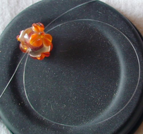 Threading the bead to attach it to necklace without crimps.