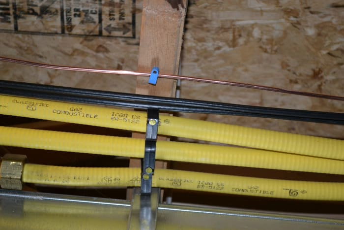An example of the CSST gas line being properly secured to an overhead beam on our basement ceiling