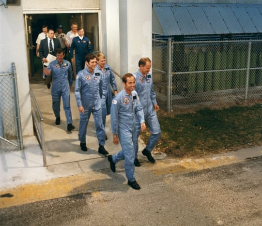 """Traditional exit from the crew quarters to the """"AstroVan"""" for the 11-mile trip to the launch pad."""