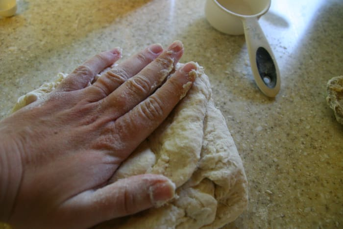 Place the dough ball on the counter. Press the dough out with your hand.