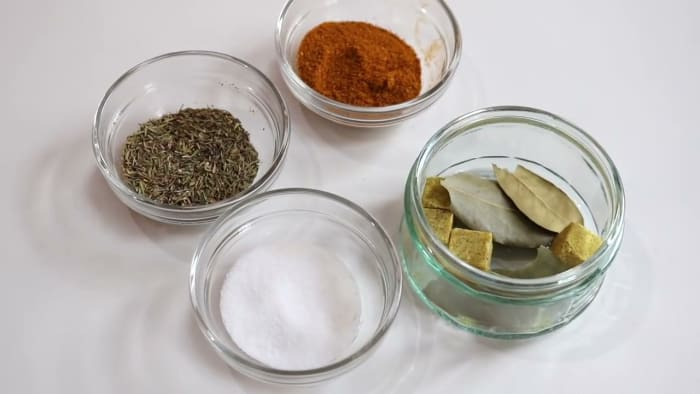 Clockwise from top: Jamaican curry powder. bay leaf, kosher salt, and dry thyme