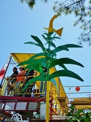 View of some band members and a metal tree with a yellow bird on top of it.