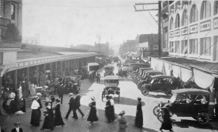 Scene in Pike Place Market c. 1915. Looking roughly northwest on Pike Place. At left, Main Market (later rebuilt as Main Arcade). At right, Corner Market and Sanitary Market. In distance, Washington National Guard Armory.