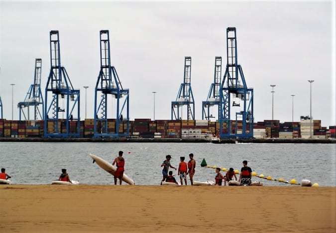 The cranes and freight containers of Puerto de la Luz across the water from Playa de las Alcaravaneras.