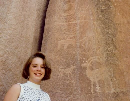 Photo of my niece standing in front of some petroglyphs