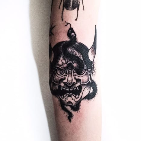 A hannya mask tattoo that incorporates a snake.