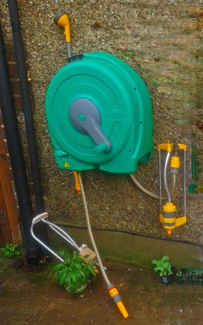 This is my Hozelock reel hanging on the wall, with various attachments - a spray head (above) and a garden sprinkler (below)