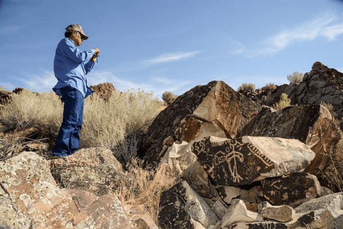 Rupert Steele, of the Confederated Tribes of the Goshute Reservation, takes a photo during a tour of a petroglyph site in Box Elder County, Utah, Aug. 26, 2016.