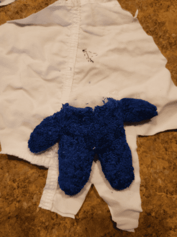 Glue your stuffed animal in place to the back of the fabric. Then cut excess fabric.