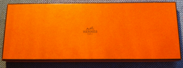 Real Hermès tie boxes are a distinctive bright orange.  Fakes will be off-color and may not have the same font on the printing.  This one is legit!