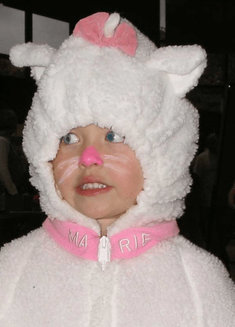 Very simple face paint for a small child. Pink nose and lips, white whiskers.