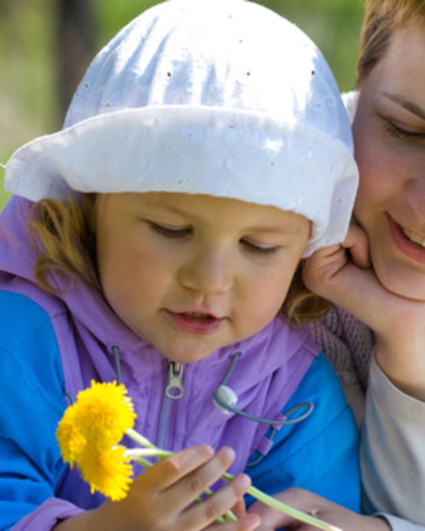 Mother and preschool-aged daughter holding dandelions