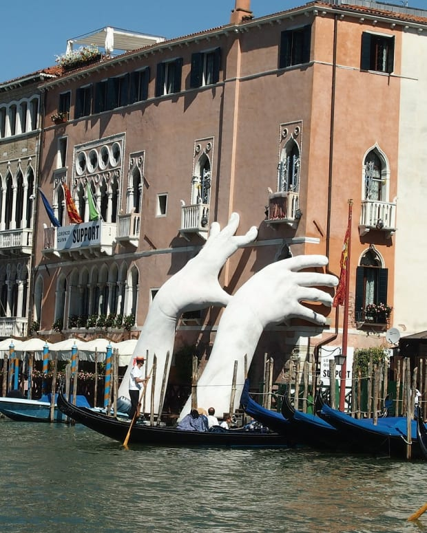 Sculpture of Hands in Venice raising concern about the sinking of the city.