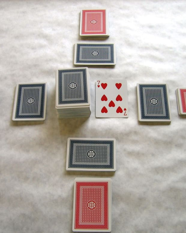 The table is set for play. Front hands in red, back hands in blue. The pick up and discard piles are in the center. Players may only look at their front hand cards first, and may not look at the back hand until they have played through the front hand