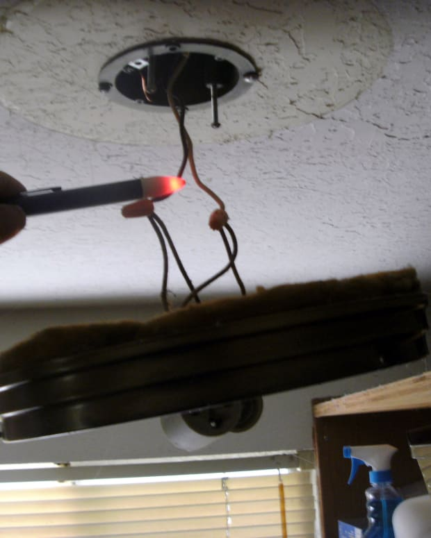 "Testing for ""hot"" wires with a voltage detector when changing a light fixture."