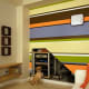 This modern accent wall with horizontal stripes in varying colors and widths is a great example of how painting only one wall can have a dramatic effect in a room.  Photo is courtesy of http://www.flickr.com/photos/dansays