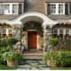 Exquisite stone example with covered front porch, wood shutters, and windows with mullions.