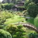 Japanese Zen—typified by peaceful, curving shapes of green rolling hills, round-canopied trees and bushes, and bridges over streams of slow-moving koi.