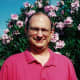 My hubby standing against our pink oleanders
