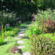 A flagstone path beckons visitors to explore around the bend of the perennial border.