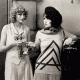 Joyce Compton and Clara Bow with longer curly bobs.