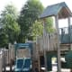 More play equipment made of natural and artificial materials, located in a semi-natural playground in a park