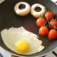 Egg is fried with the tomatoes and mushrooms.