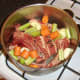 Vegetables and seasonings are added to beef and bones