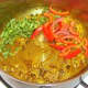 Chopped vegetables are added to sauteed spices