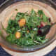 Peach and salad leaves are added to bowl with marinade