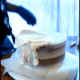 Start smoothing around the sides and top, giving an even layer all the way around the entire cake.