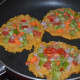 Step three: Heat some oil in a pan. Pour a table spoon batter on the hot pan. Gently spread it a little. Top it with mixed vegetables. Make three such pancakes on the pan.