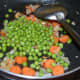 Step four: Throw in green peas and salt.
