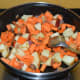 Step four: Throw in chopped carrots and apple. Add some salt. Stir-cook for 4-5 minutes.