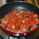 Step four: In the same pan, add chopped tomatoes. Stir-cook on a high heat for 4 minutes. Add cooked carrots. Mix well. Turn off the heat. Transfer it to the same mixer/blender in which you have collected the sauteed spices.