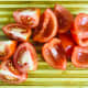 Quarter each tomato and remove the seeds. This is done easily by placing the tip of the knife at the bottom and running it under the seeds towards the stem end with the knife parallel to the tomato.