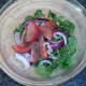 Watercress salad ingredients are seasoned and combined in a bowl