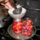 """Ladle hot syrup into each jar to cover plums, leaving 1/2"""" headspace."""