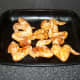 Marinated chicken wings are laid in a single layer on a large roasting or baking tray