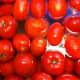 Tomatoes in sink covered with boiled water so peelings will slide off.