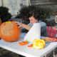 Carving their pumpkins into jack-o-lanterns