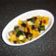 Roasted vegetables are laid in the base of a serving dish