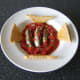 Fresh sardines cooked in homemade tomato sauce are served with hot, buttered toast.
