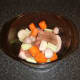 Pork and vegetables are added to casserole dish and seasoned