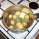 Butter and chopped mint are added to drained potatoes