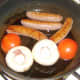 Frying sausages, mushrooms and tomato
