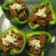 Top the stuffed peppers with shredded cheese.