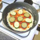 Tomato sauce and vegetable slices are added to pizza omelette
