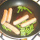 Green beans are added to fried sausages